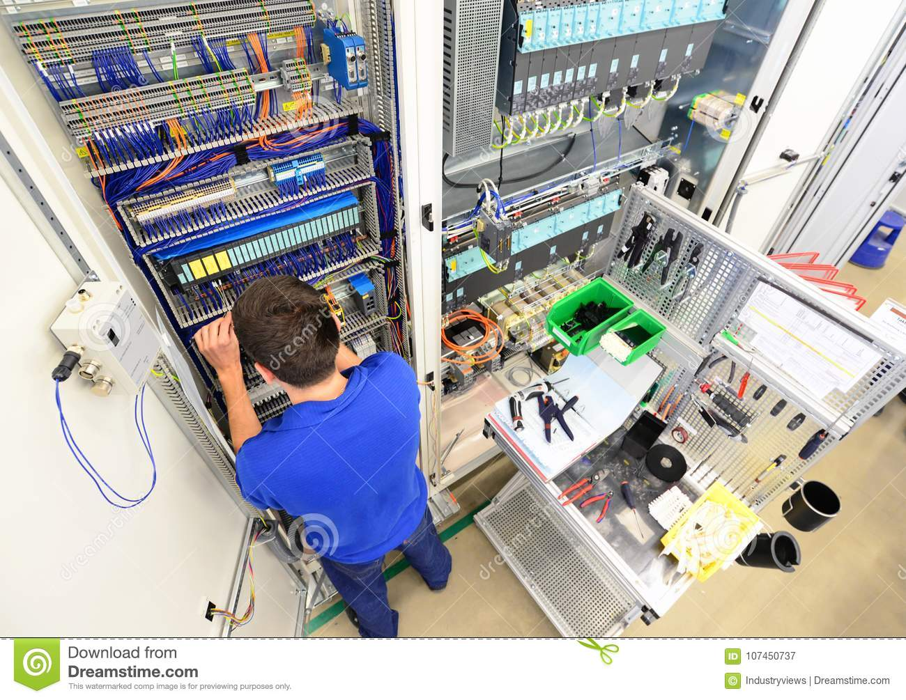 man assembles electronic components on a machine in a factory for mechanical engineering