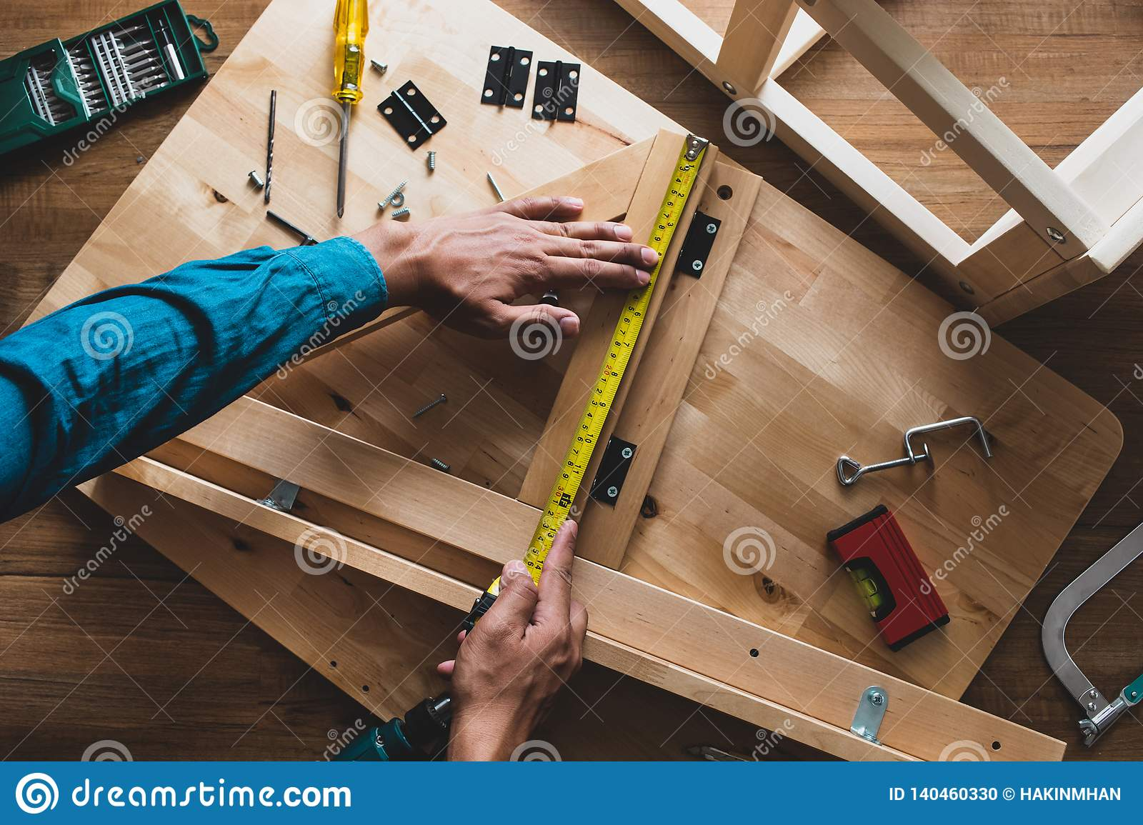 Man Assembly Wooden Furniturefixing Or Repairing House With Yellow