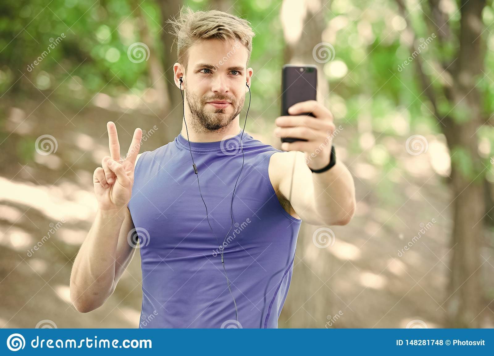 Man athlete concentrated face take smartphone photo nature background. Sportsman take photo winner sport competition