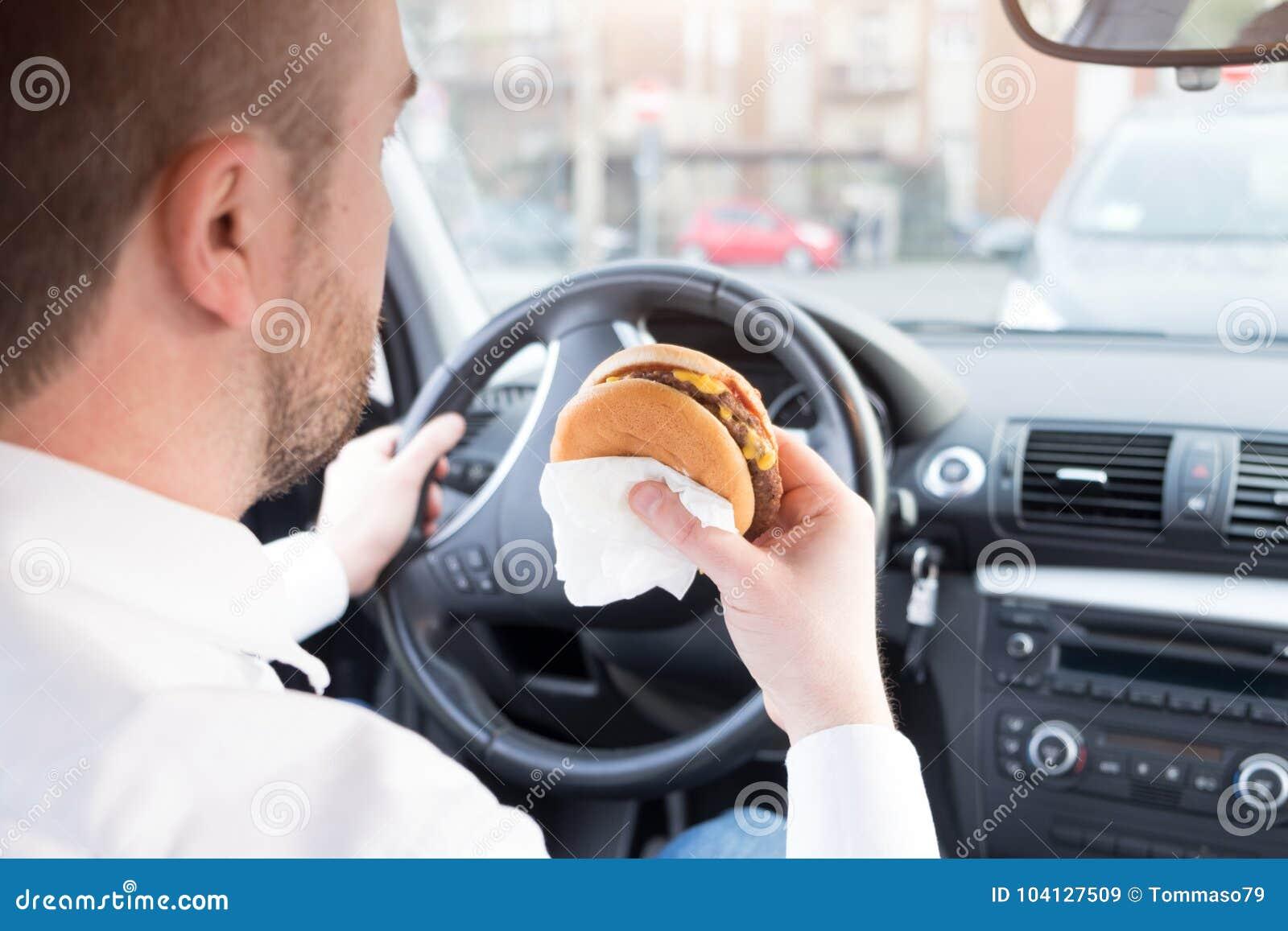 Man att äta skräpmat och körning som placeras i bil