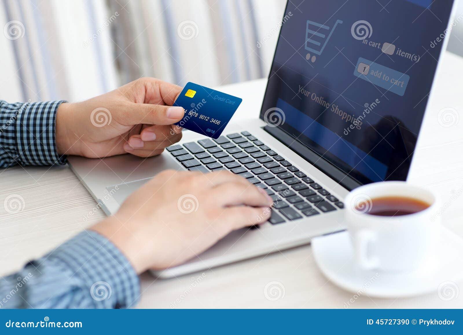 Man att göra online-shopping med kreditkorten på bärbara datorn