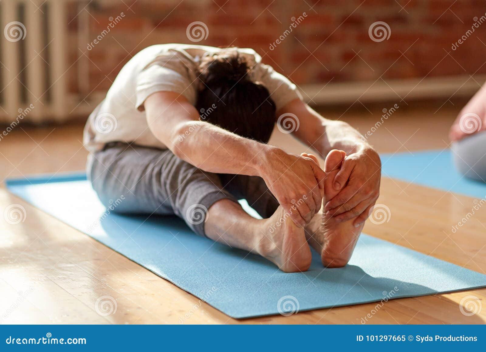 Man att göra yoga böjer framåtriktat på studion eller idrottshallen