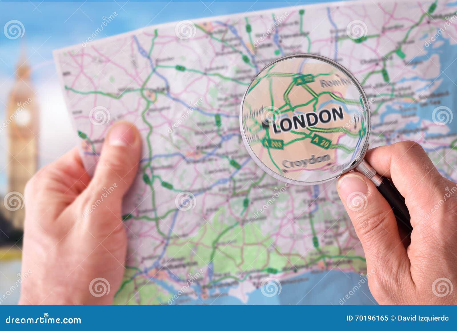 Man att konsultera en översikt av London med ett förstoringsglas