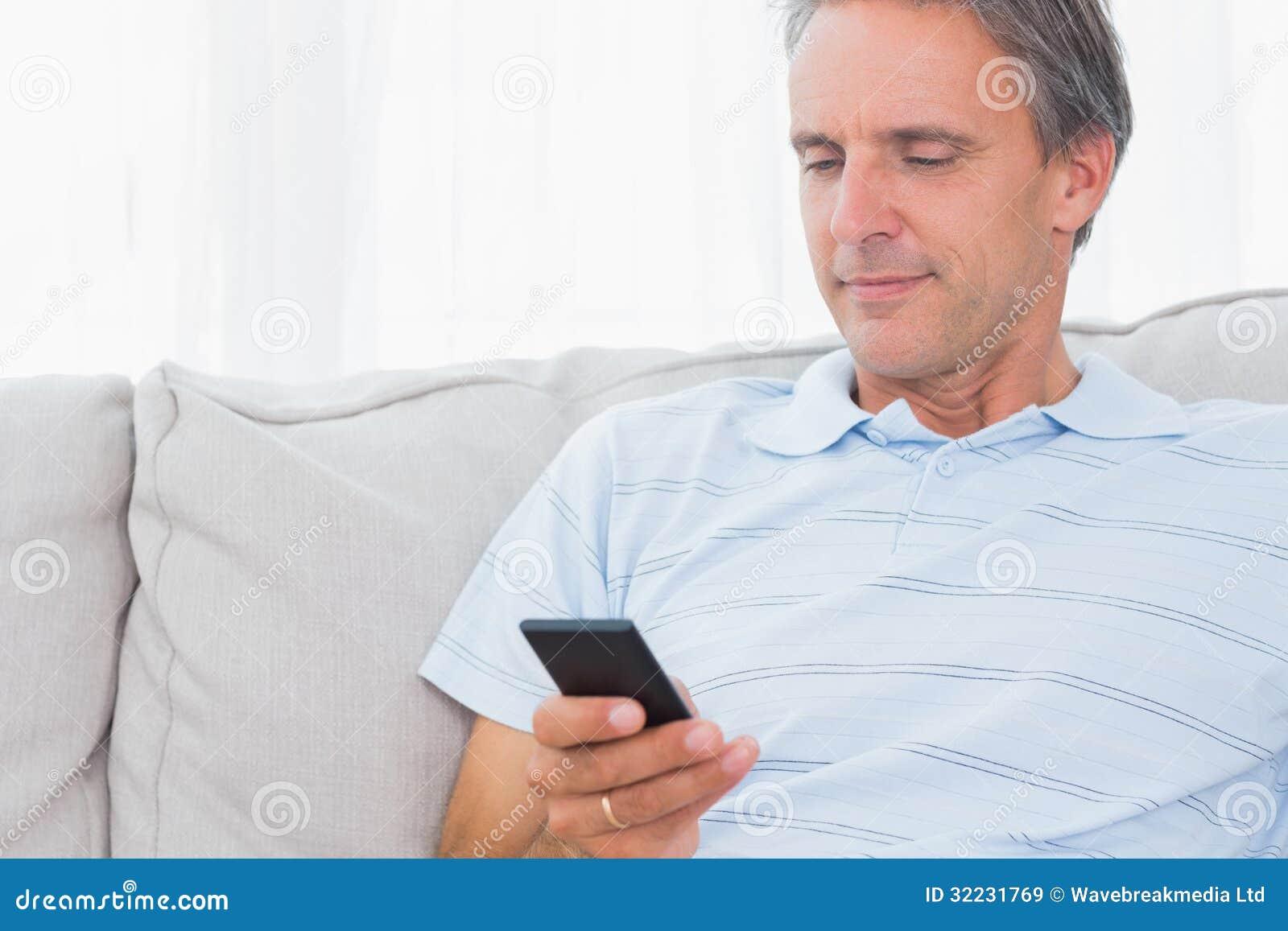 Man att koppla av på hans soffa som överför en text