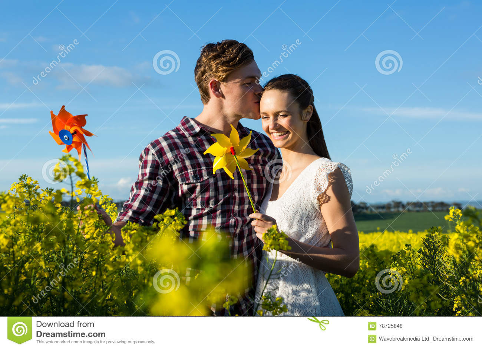 Man att kyssa på kvinnapannan i senapsgult fält