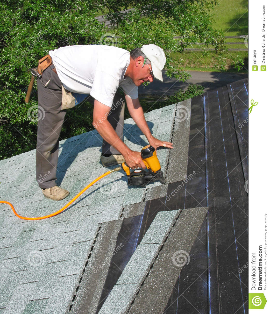 Man attaches shingles to roof