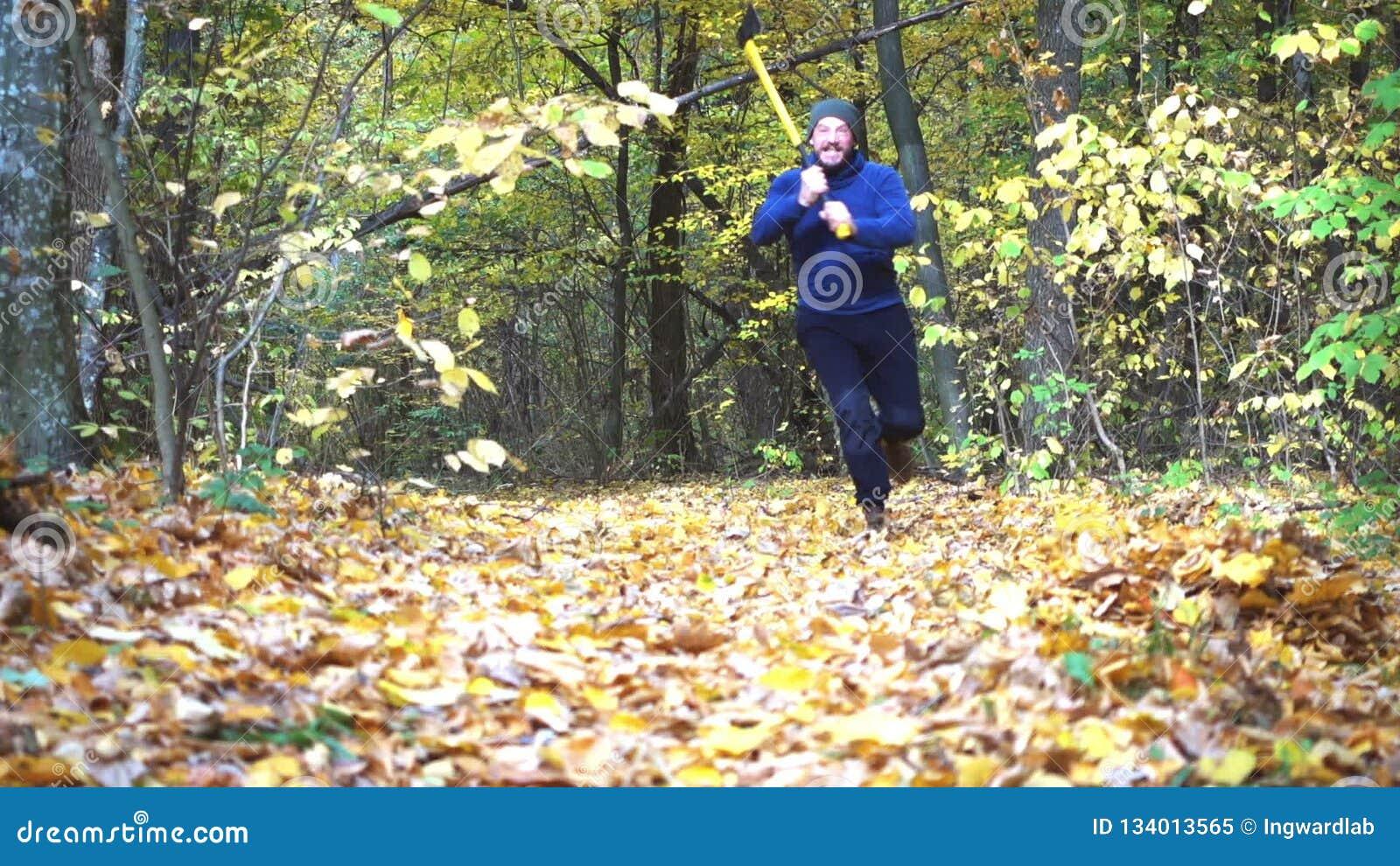 A man with an ax runs slowly towards the camera. Bearded man runs with an ax to the camera. A man with an ax runs slowly towards the camera stock video