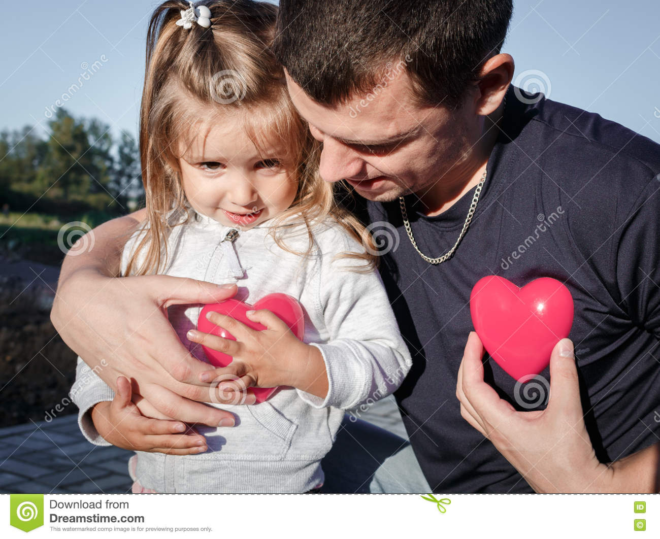 Man and baby holding a two red plastic heart. father hugs the daughter