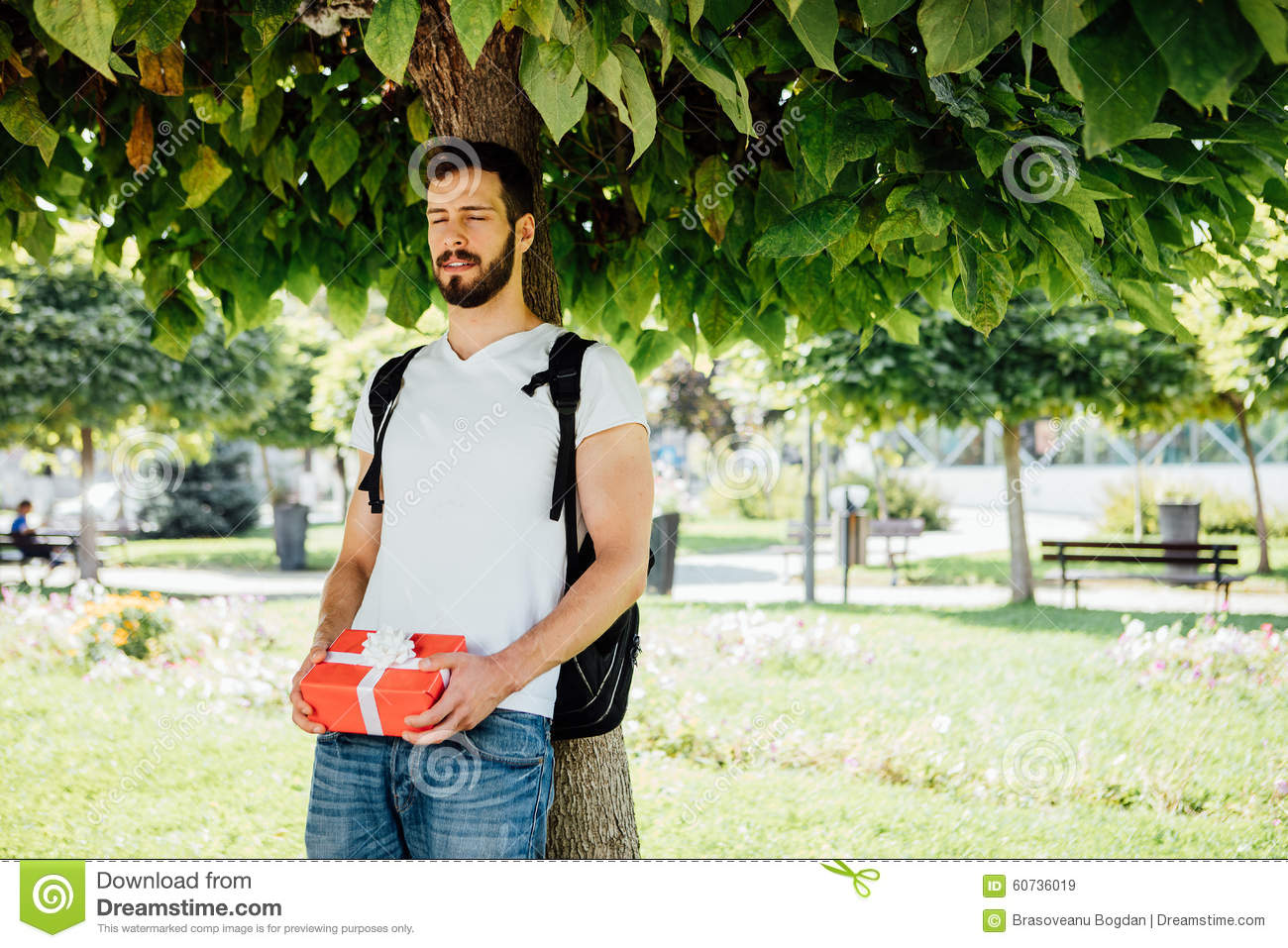 Man with backpack and a gift next to a tree