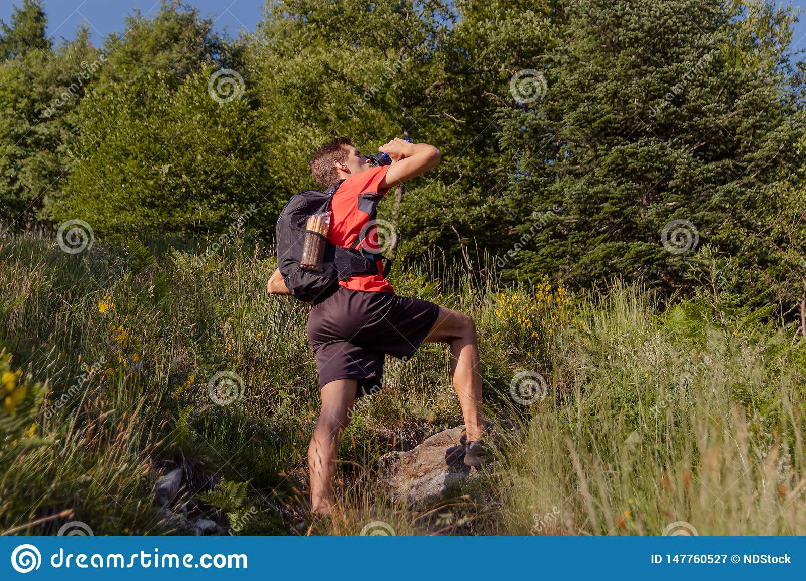 Man with backpack take a rest and drinking from water bottle during a hike
