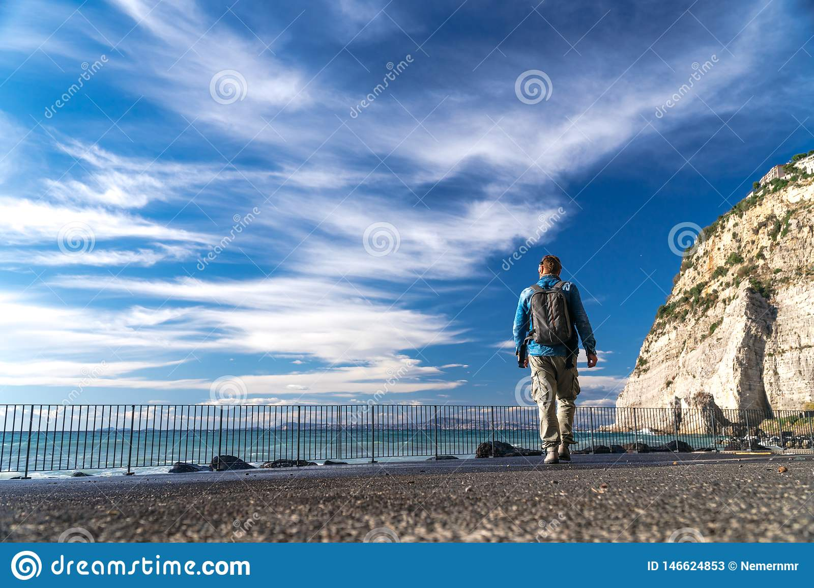 Man with backpack walk alone and watching on the water strong waves, clouds and mountains bacground, Sorrento Italy