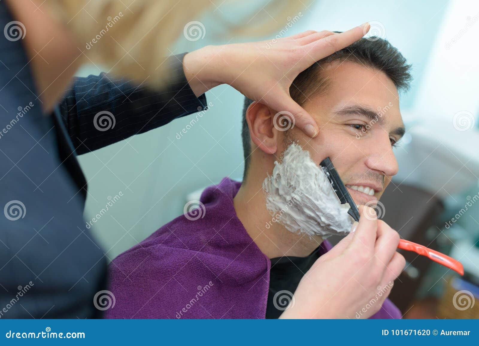 Man barber shaves customers beard
