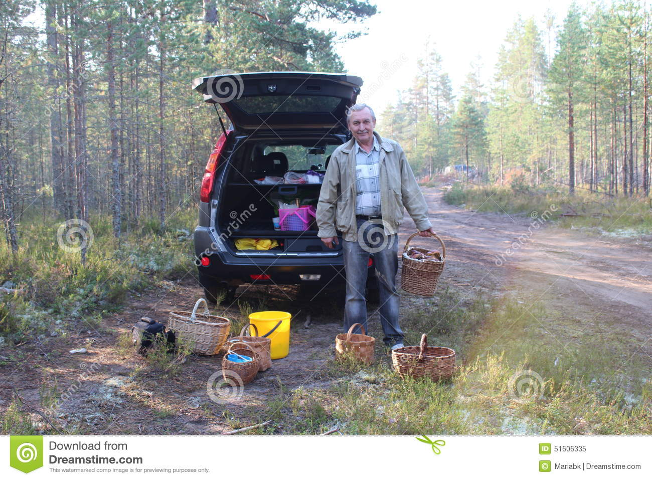 Man with a basket of cepes mushrooms in the forest and a car on background