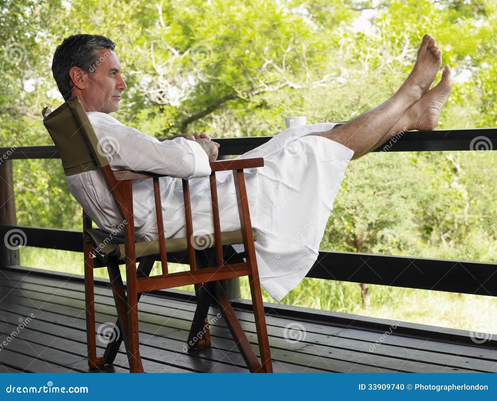 Man In Bathrobe Sitting Terrace With Feet Up Stock