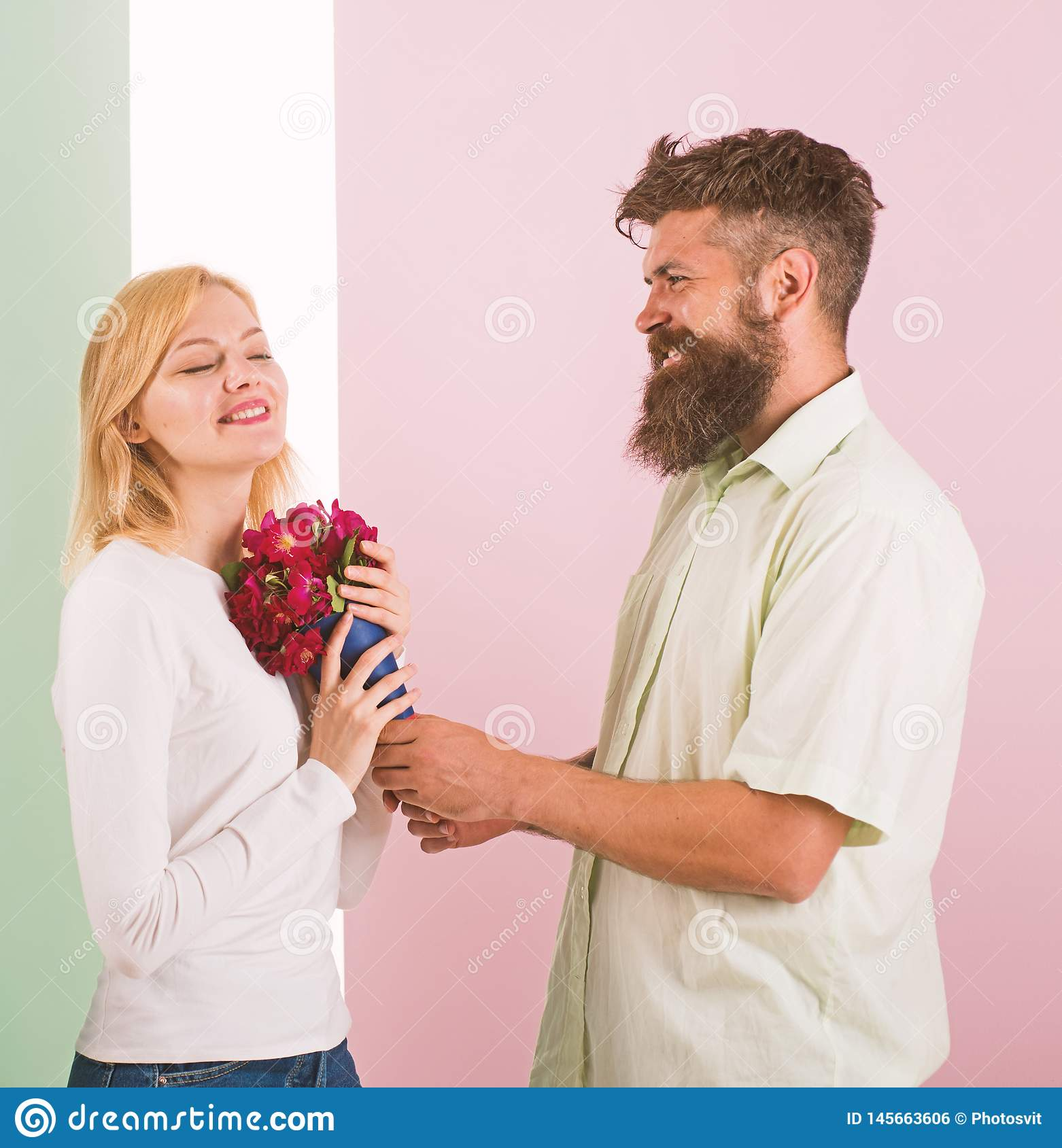 Man with beard congratulates woman birthday anniversary holiday. Hipster bearded give bouquet flowers to girlfriend