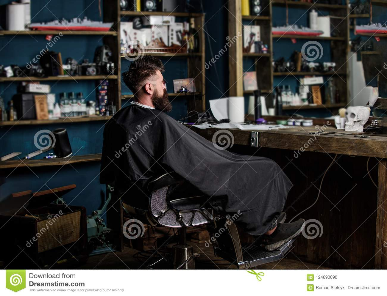 Man with beard covered with black cape sits in hairdressers chair in front of mirror. Man with beard client of hipster
