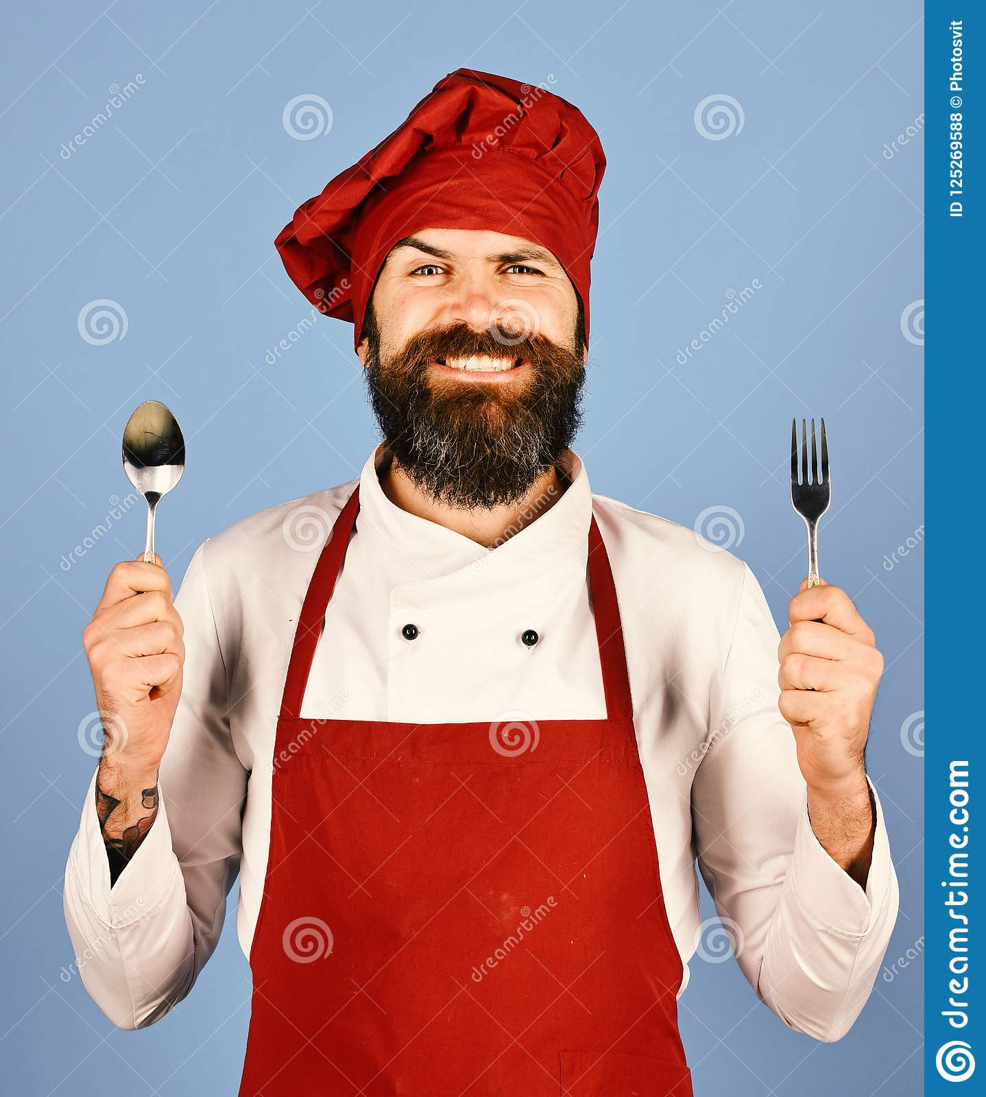 Man with beard holds kitchenware on blue background. Chef holds cutlery. Professional cookery concept. Cook with happy