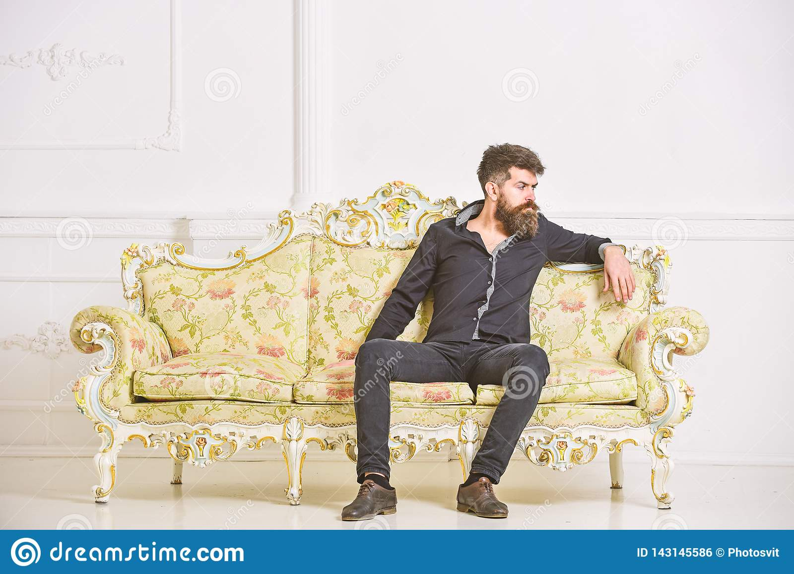 Man with beard and mustache spends leisure in luxury living room. Hipster on thoughtful face sits alone. Rich and lonely