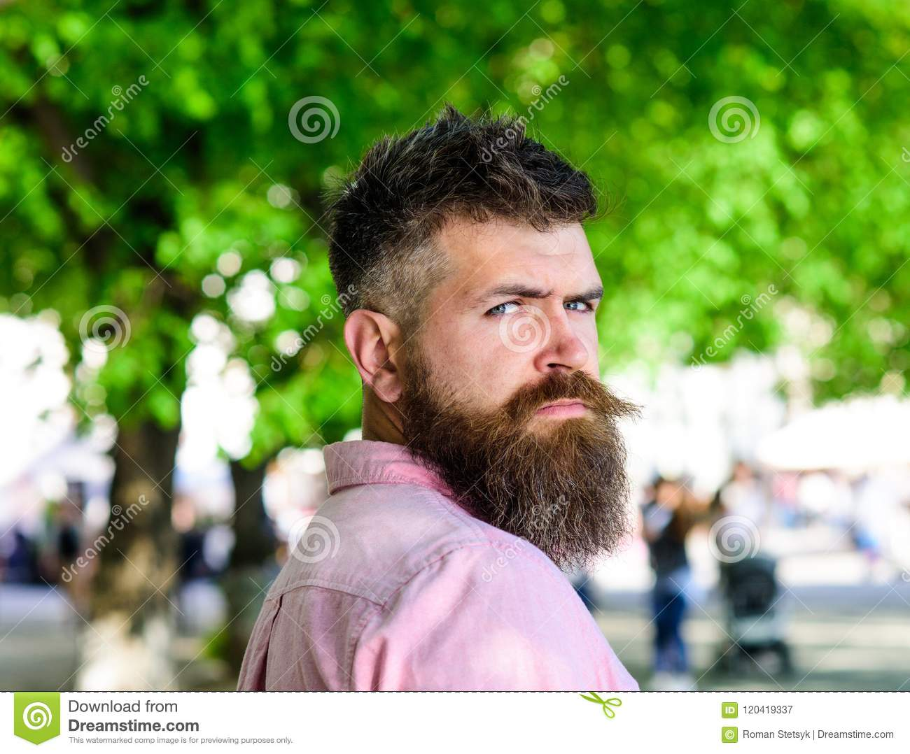 Man With Beard And Mustache On Strict Face Looks Back While Walks In