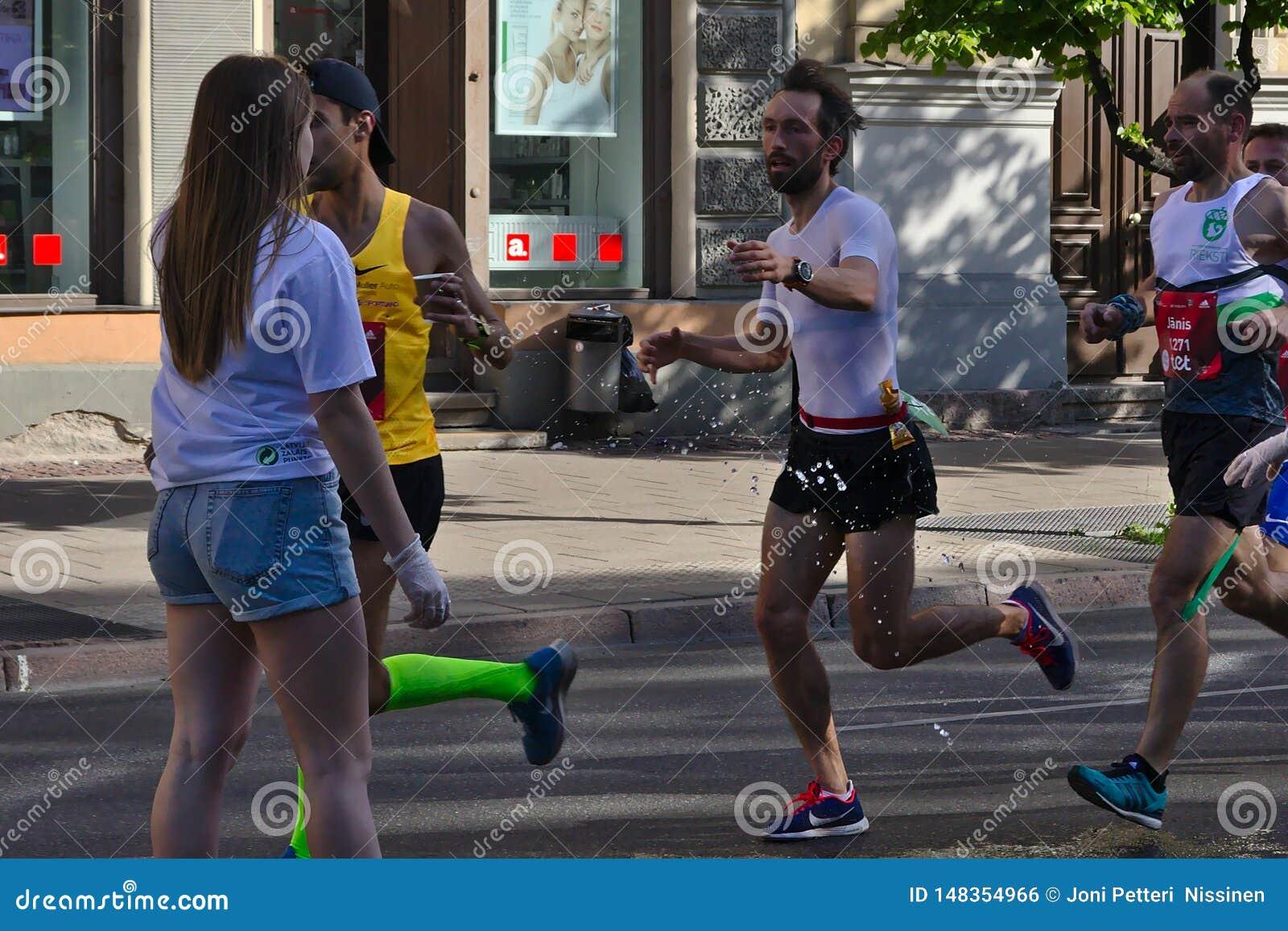 Riga, Latvia - May 19 2019: Man with beard reaching for refreshment