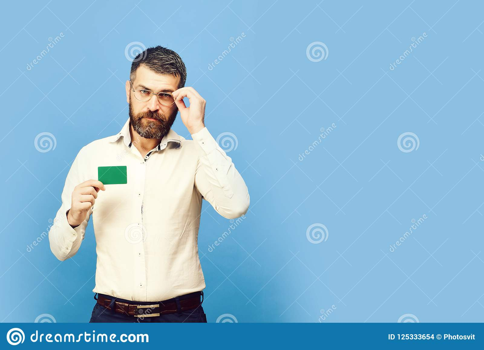 Man with beard in white shirt holds green business card. Guy with smart face with glasses isolated on blue background