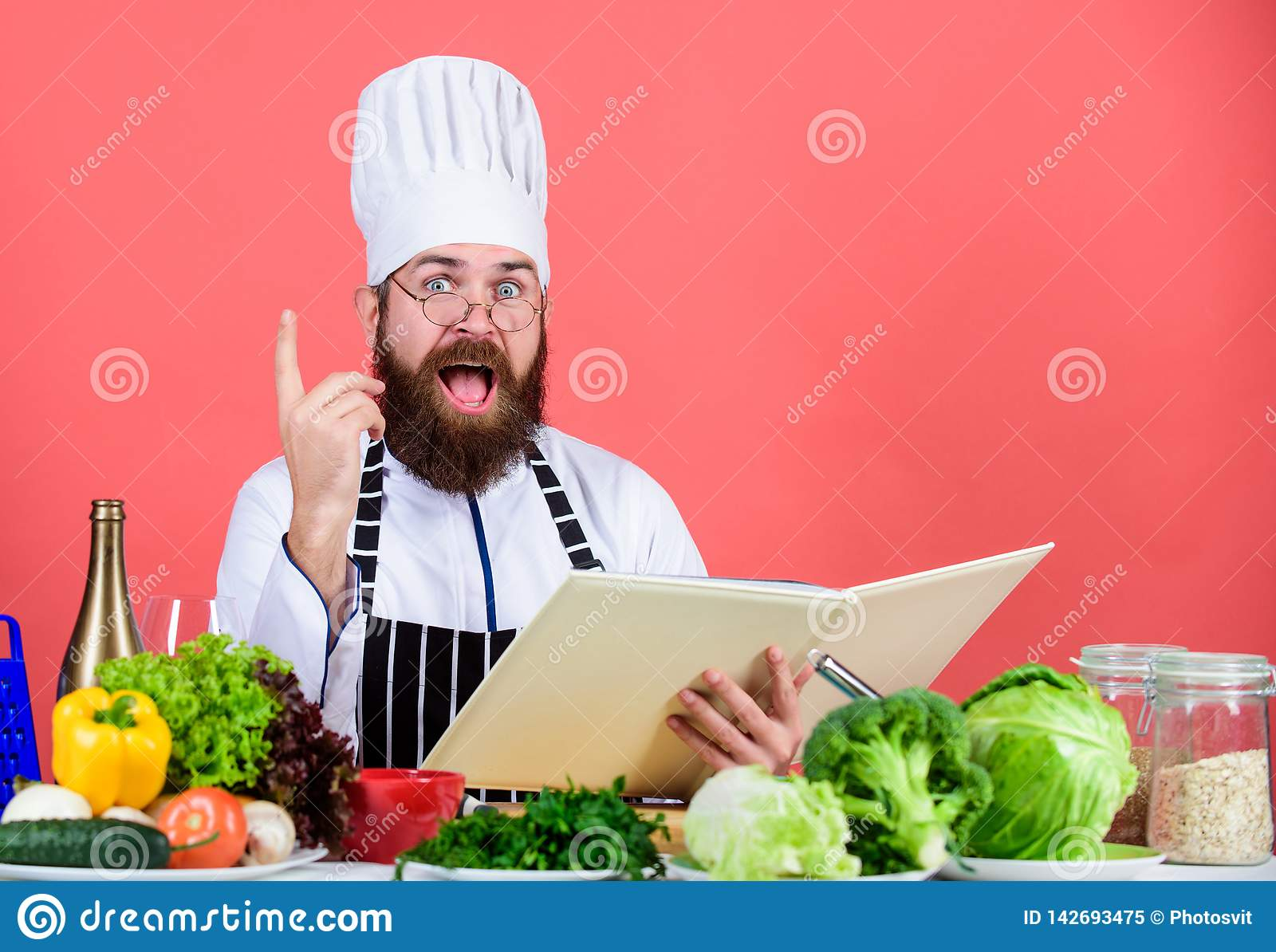 Man bearded chef cooking food. Culinary arts concept. Amateur cook read book recipes. Man learn recipe. Try something