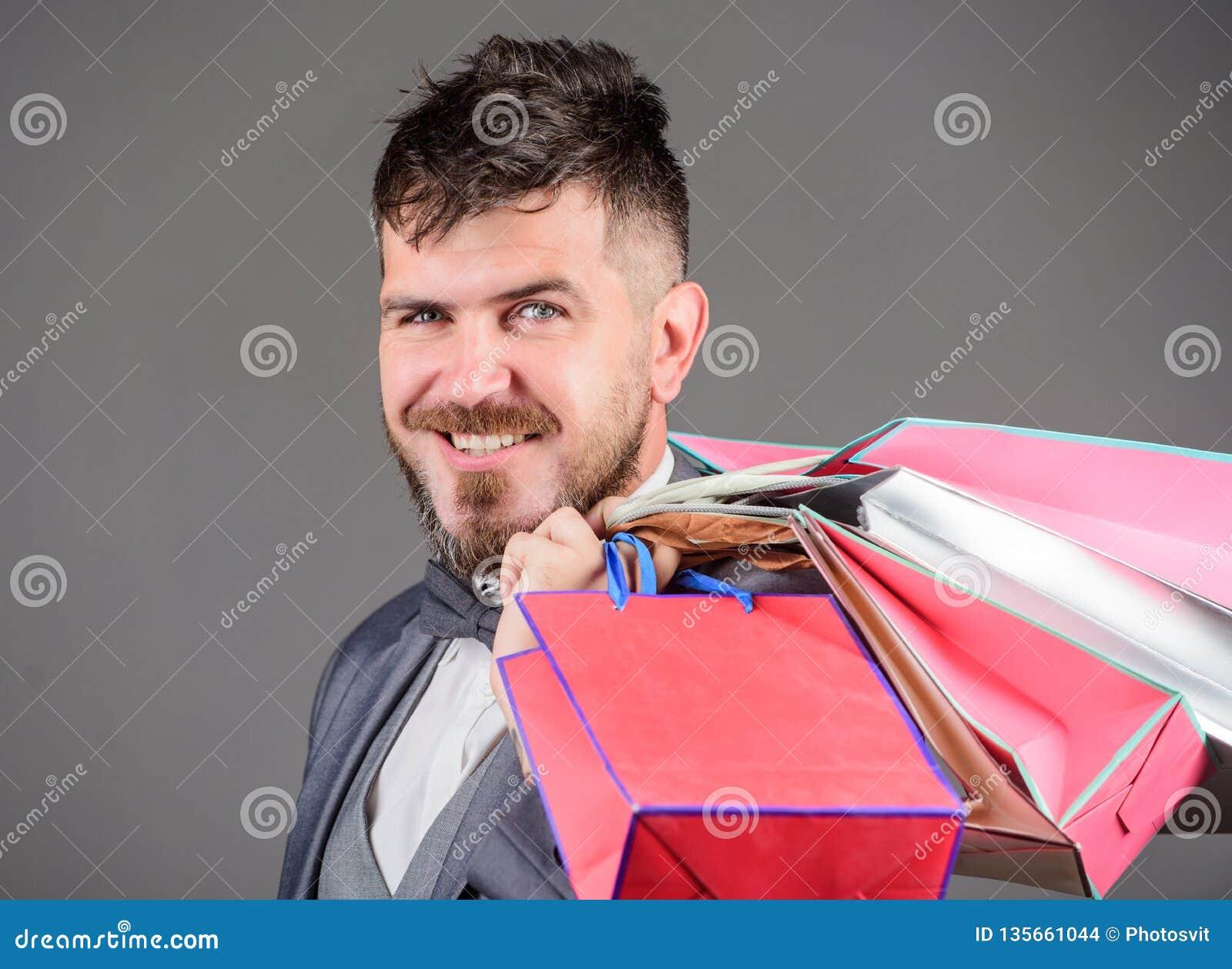 Man bearded elegant businessman carry shopping bags on grey background. Make shopping more joyful. Elite boutique. Enjoy