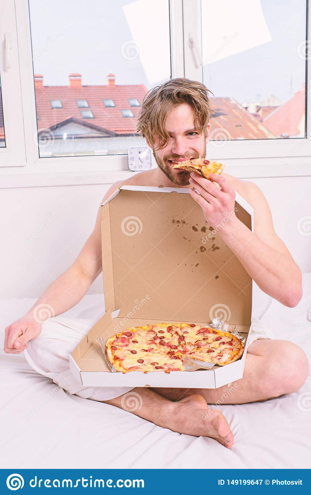 Man bearded handsome eat pizza. Man eat pizza breakfast. Guy naked covered pizza box sit bed bedroom offer you join him