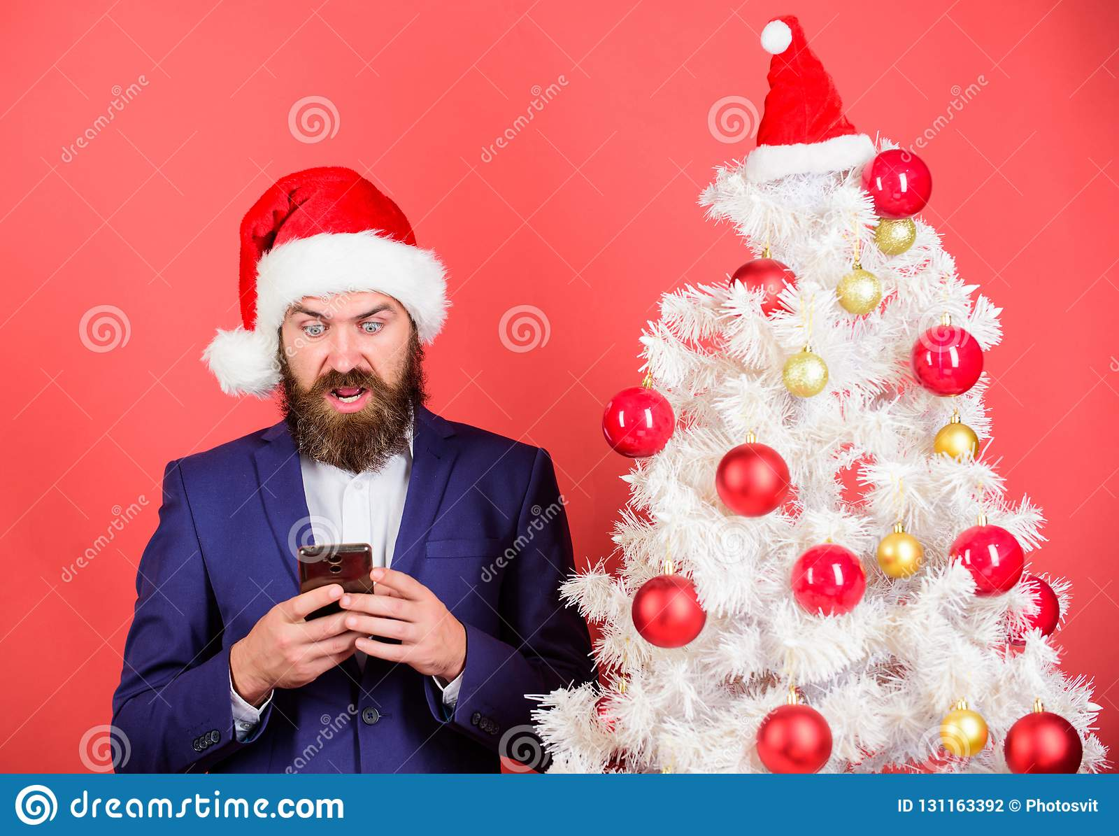 Man bearded hipster wear formal suit and santa hat hold smartphone. Send christmas greeting mobile message. Short