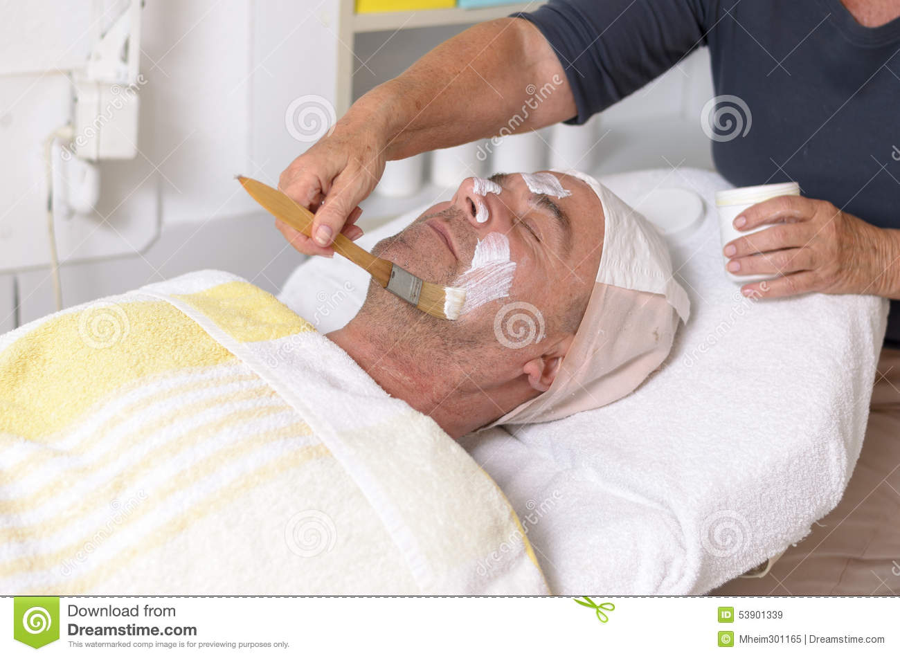 Man at beauty center receiving facial treatment stock for Beauty treatment bed