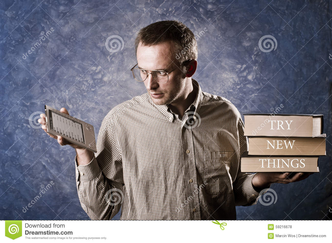 Man being focused on light and handy ebook reader, holding heavy books in other hand, try new things written on books.