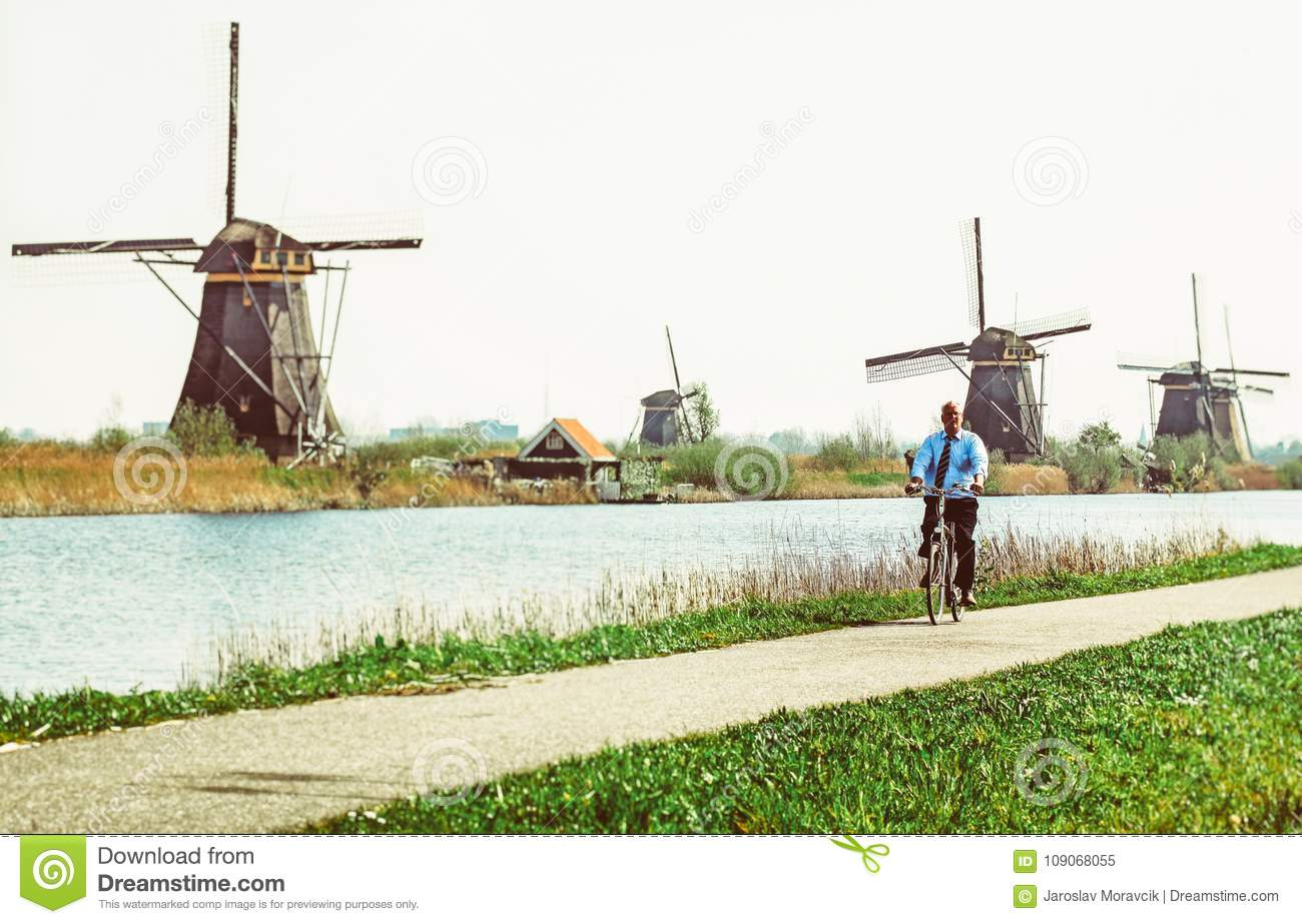 Man on bicycle and windmills at Kinderdijk, Netherlands