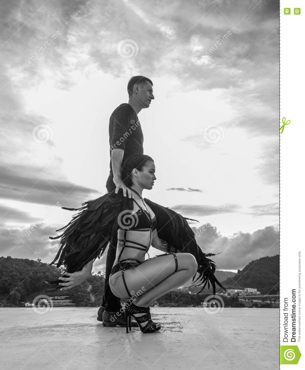 Black and white photo of romantic scene with men and sensual angel women standing on the rooftop over sky background