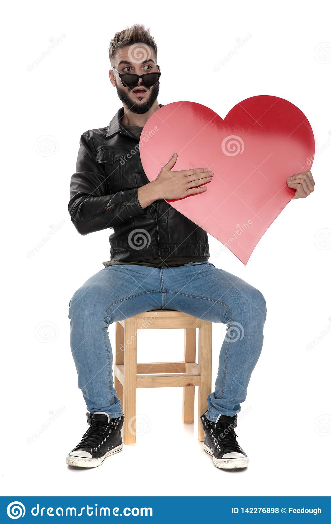Man holding a red heart on hand while looking amazed