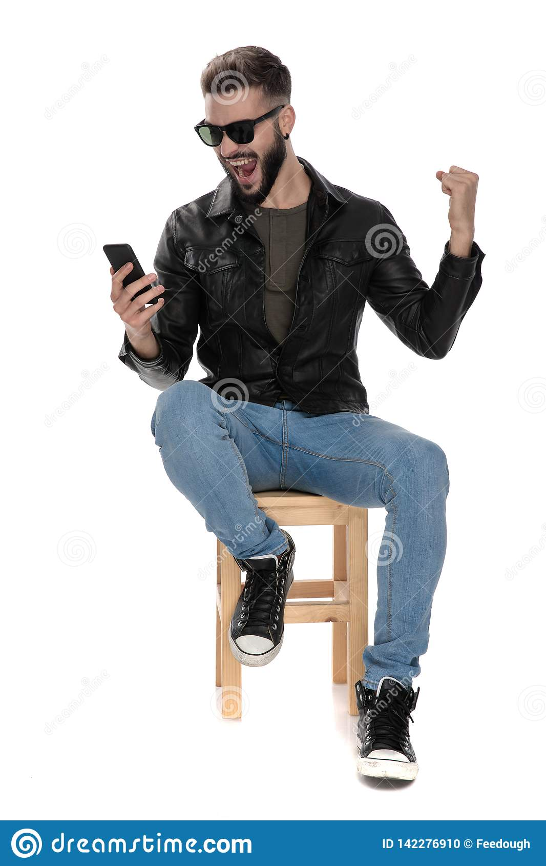 Man sitting on chair while looking at phone celebrating