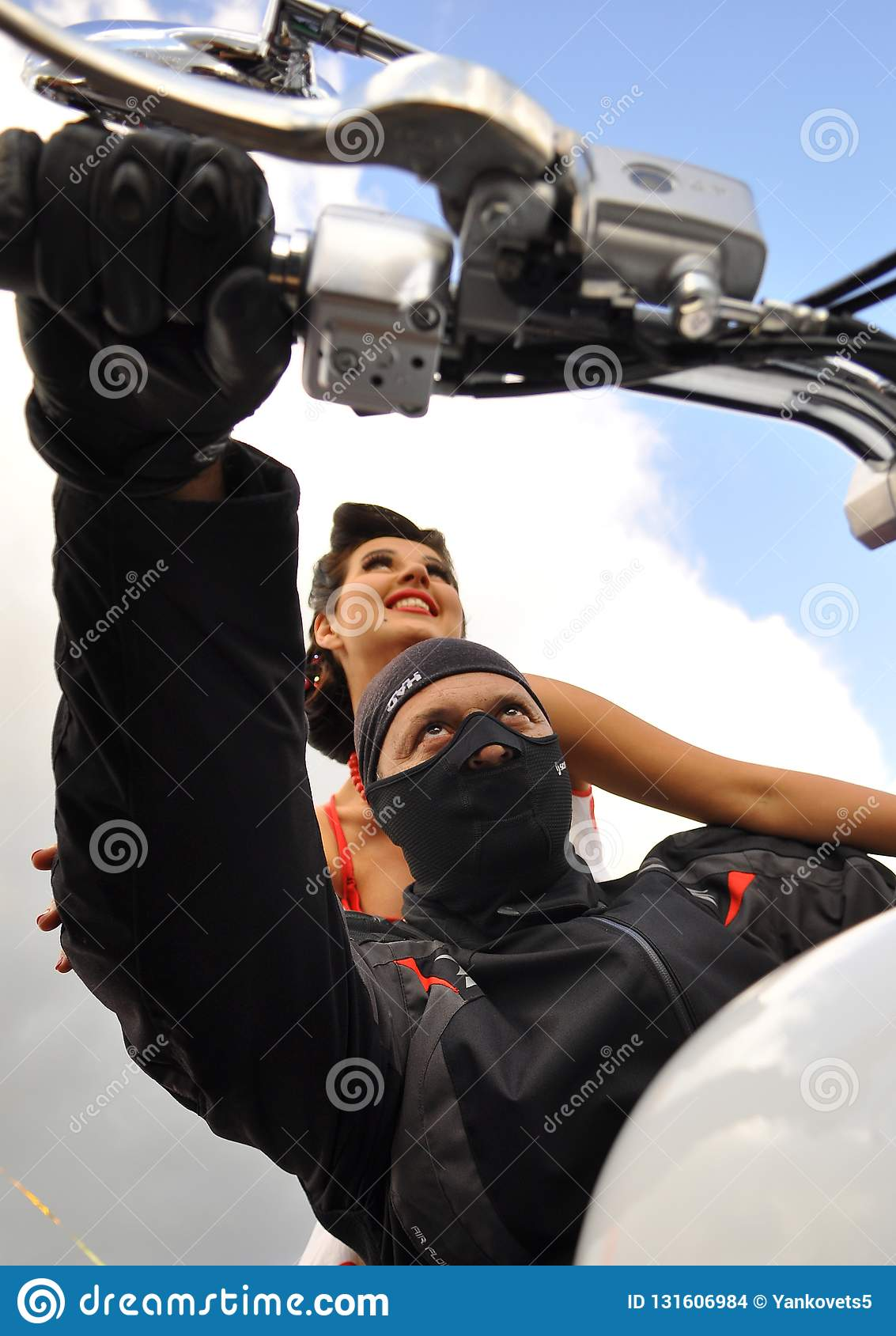 A man in a black mask sits behind the wheel of a white motorcycle behind him sits a beautiful girl on a background of the blue sky