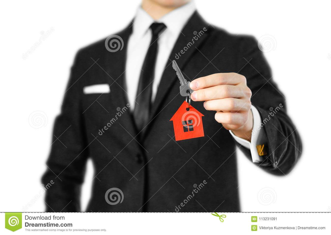 A man in a black suit holds the keys to the house. Key ring red