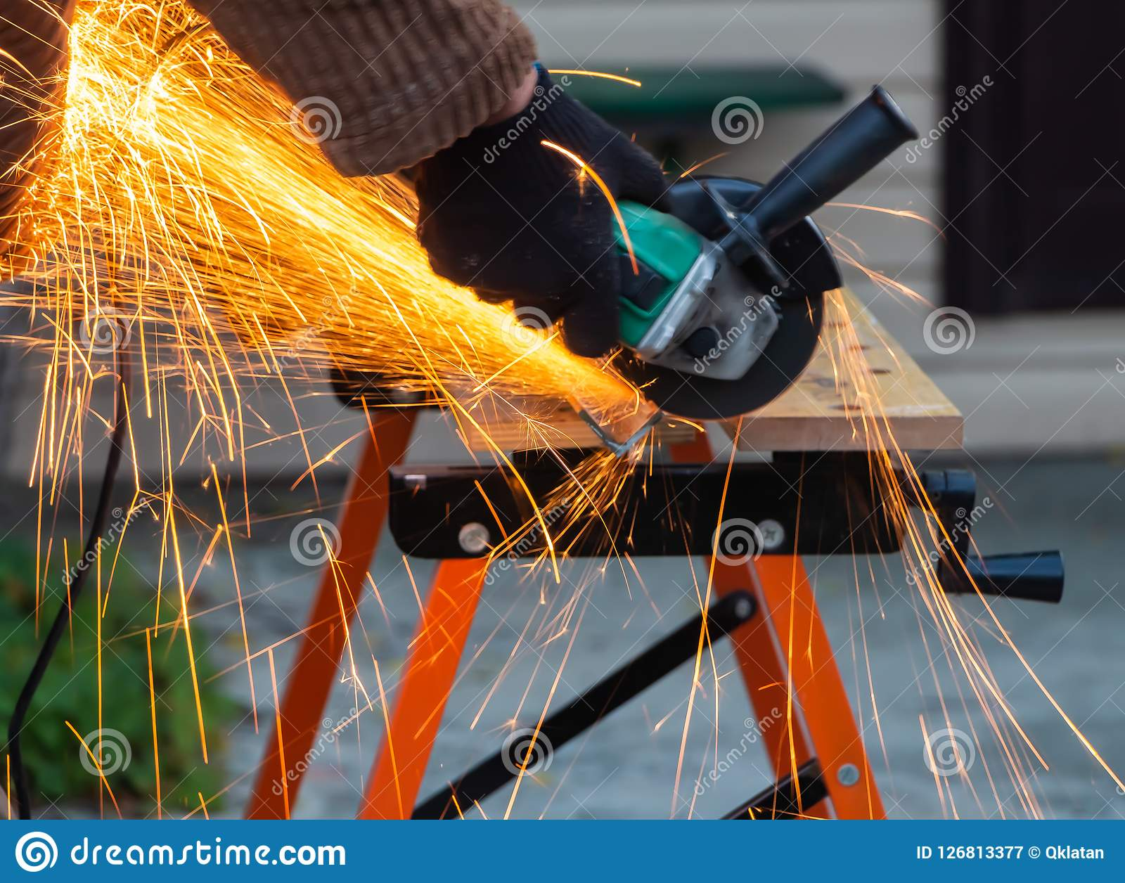 A man in the black working gloves cuts metal using an angle grinder tool with beautiful yellow sparks on a work bench