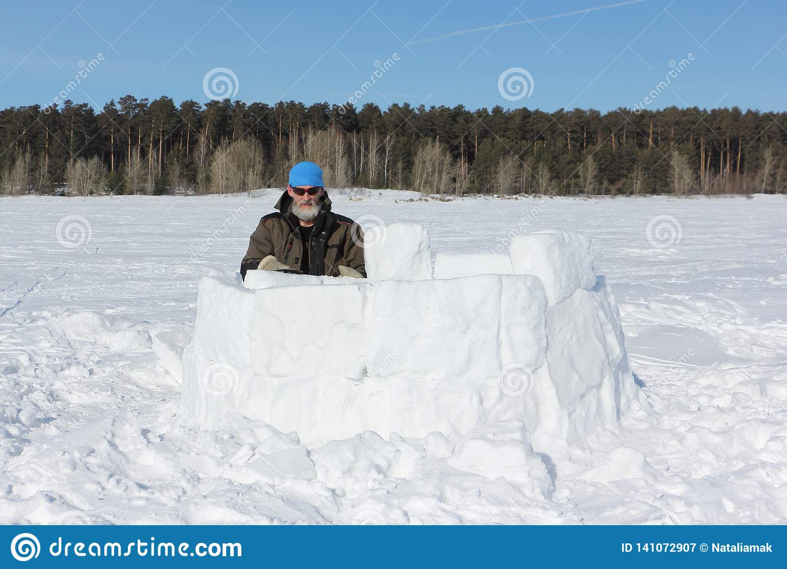 71021f515 Man In A Blue Hat And Sunglasses Building An Igloo From Snow Blocks ...