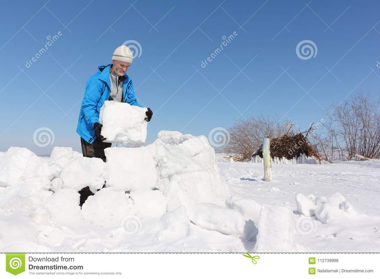 841cf0f5e Man In A Blue Jacket Building An Igloo On A Glade Stock Photo ...