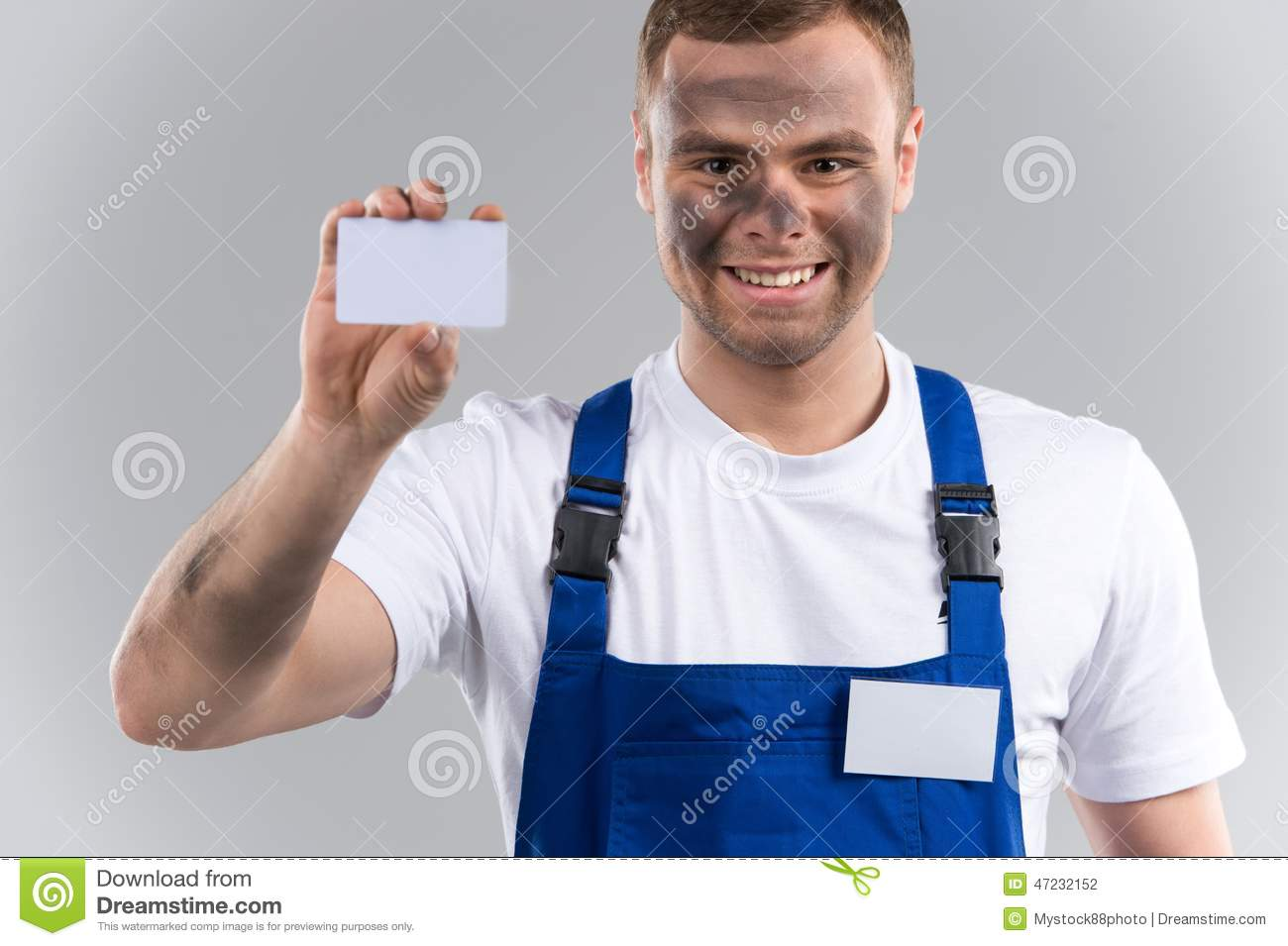 Man In Blue Overalls Holding Business Card. Stock Photo - Image of ...