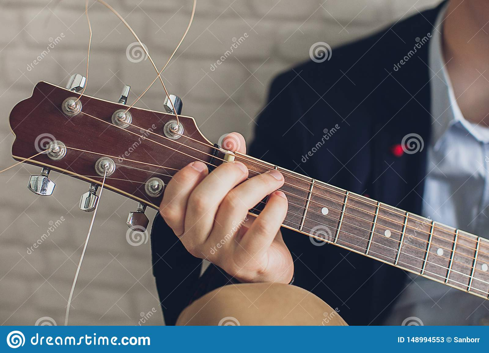 A man in a blue shirt and a dark blue jacket plays guitar against a light brick wall. Concepts Hobbies and interests in music. The
