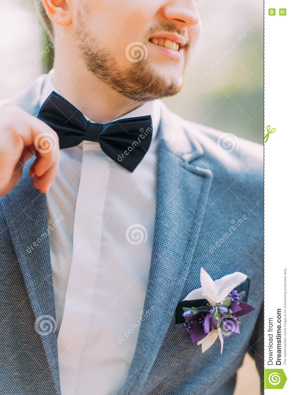 Man In Blue Suit With Black Bow Tie, Flower Brooch, And Classic ...