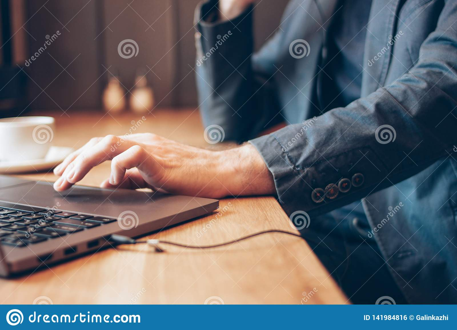 The man in blue suit with headphones working on a laptop in cafe