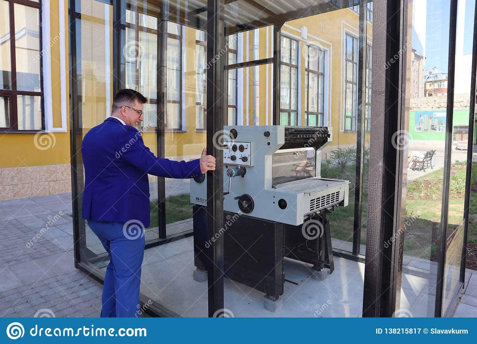 Man in a blue suit looks at the printing press behind the glass