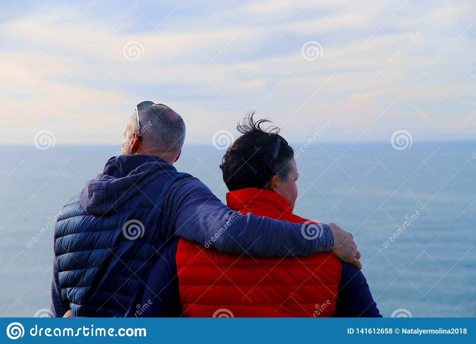 A man in a blue vest hugs a woman in a red vest against the background of the ocean and the sky.