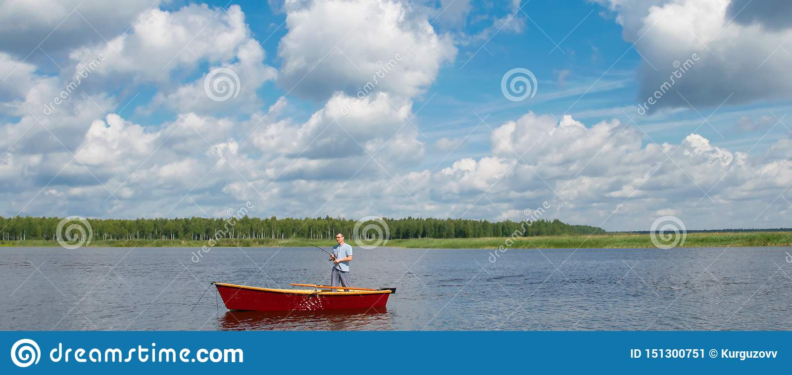 A man in a boat, in the center of the lake, holds a fishing pole to catch a big fish, against a beautiful sky