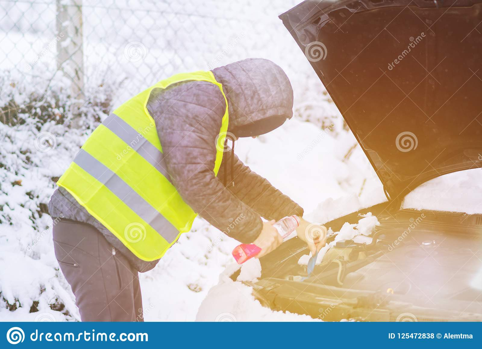 Man With Bottle Pouring Antifreeze Coolant To Car Engine At Cold