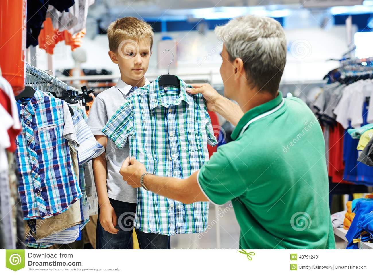 ... father choosing shirt with son boy during shopping at garments shop