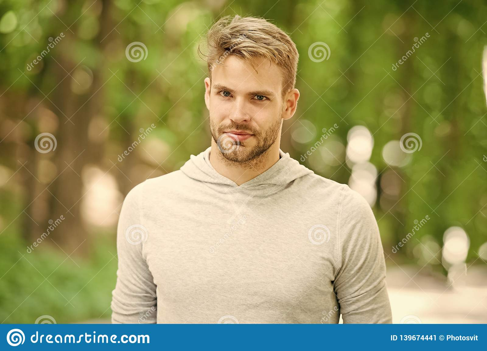 Man with bristle on calm face, nature background, defocused. Skin care concept. Man with beard or unshaven guy looks